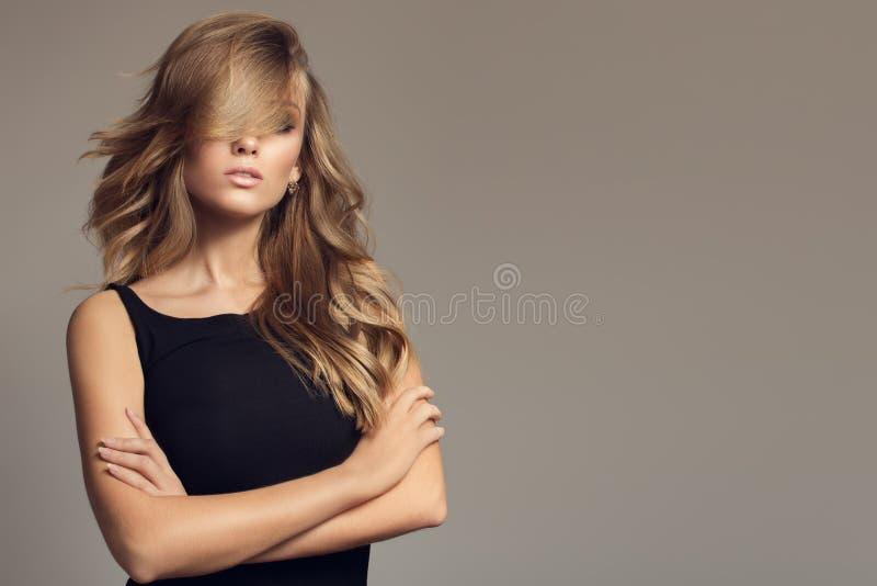 Ξανθή γυναίκα με τη μακριά σγουρή όμορφη τρίχα στοκ εικόνες