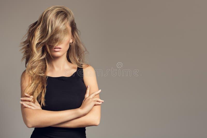 Ξανθή γυναίκα με τη μακριά σγουρή όμορφη τρίχα στοκ φωτογραφίες