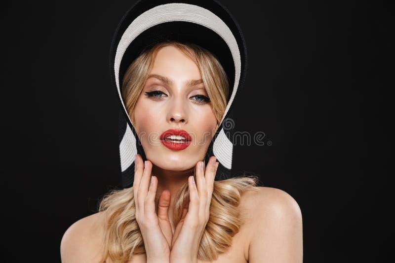 Ξανθή γυναίκα με τη φωτεινή κόκκινη χειλική τοποθέτηση makeup που απομονώνεται πέρα από το μαύρο υπόβαθρο τοίχων που φορά το καπέ στοκ φωτογραφία