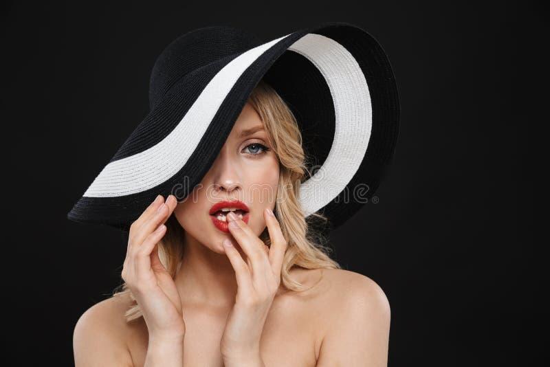 Ξανθή γυναίκα με τη φωτεινή κόκκινη χειλική τοποθέτηση makeup που απομονώνεται πέρα από το μαύρο υπόβαθρο τοίχων που φορά το καπέ στοκ εικόνες με δικαίωμα ελεύθερης χρήσης
