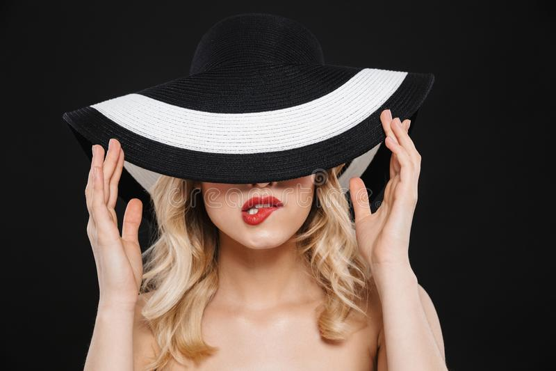 Ξανθή γυναίκα με τη φωτεινή κόκκινη χειλική τοποθέτηση makeup που απομονώνεται πέρα από το μαύρο υπόβαθρο τοίχων που φορά το καπέ στοκ εικόνα με δικαίωμα ελεύθερης χρήσης
