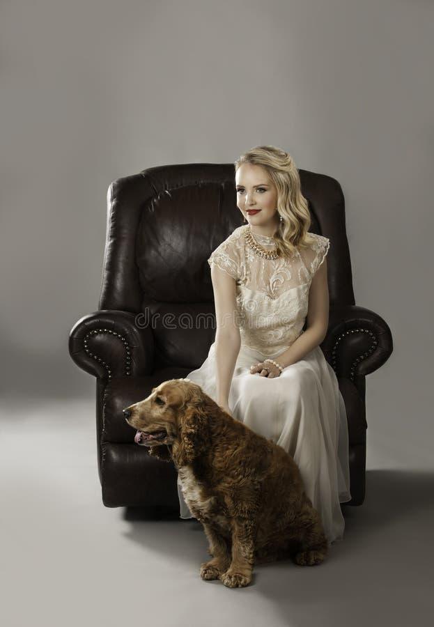 Ξανθή γυναίκα με το χαριτωμένο σκυλί στα πόδια της στοκ εικόνες με δικαίωμα ελεύθερης χρήσης