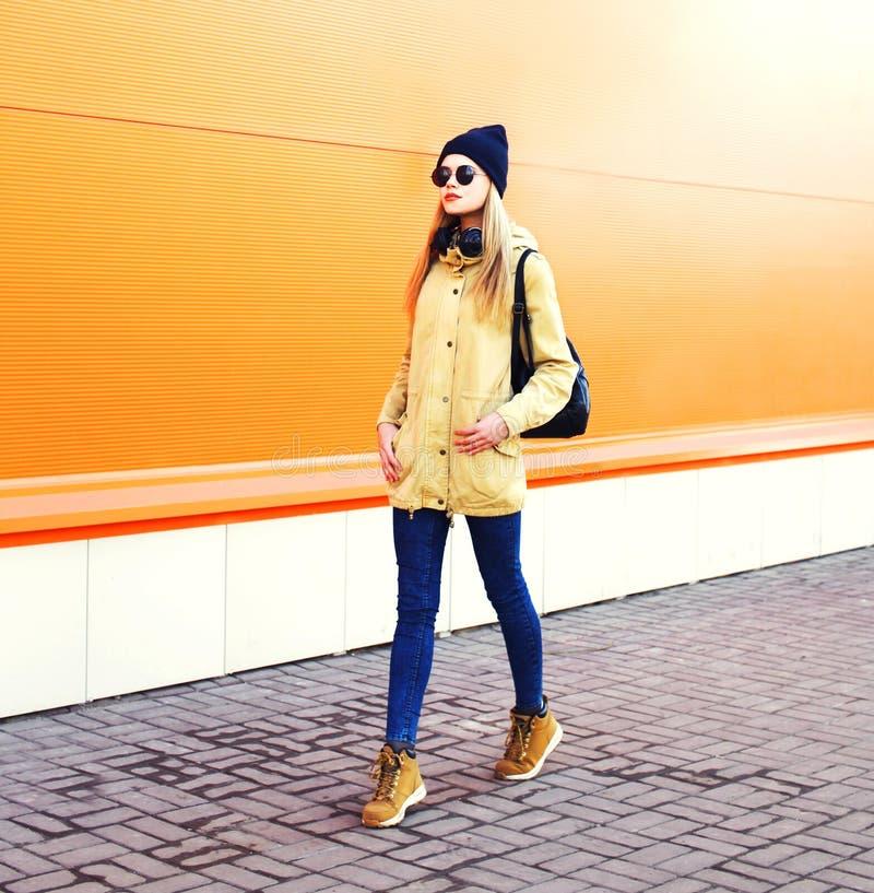 Ξανθή γυναίκα μόδας αρκετά που περπατά στην πόλη πέρα από πορτοκαλή ζωηρόχρωμο στοκ εικόνες