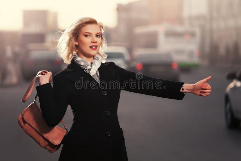 Ξανθή γυναίκα μόδας στο μαύρο παλτό που χαιρετά ένα αμάξι ταξί που περπατά μέσα στοκ εικόνα με δικαίωμα ελεύθερης χρήσης