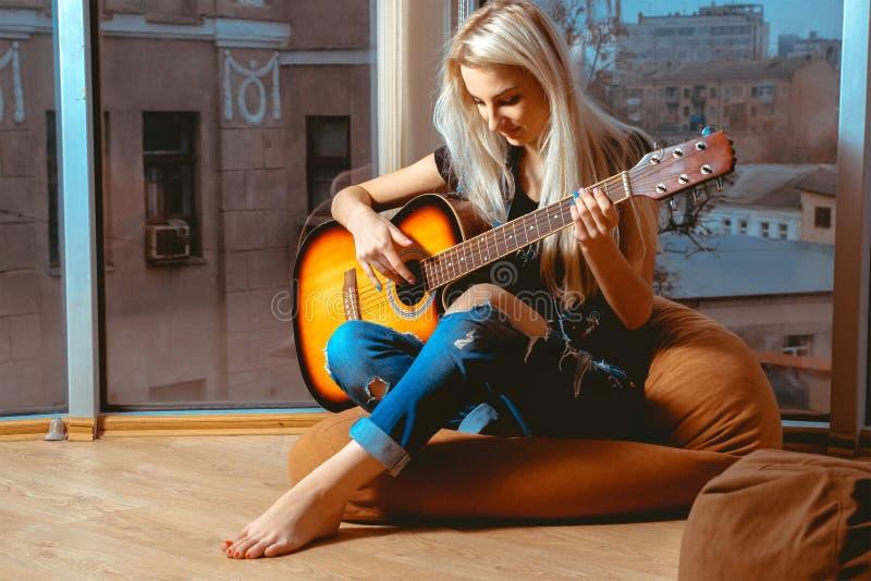 Ξανθή γυναίκα ομορφιάς που προσπαθεί να παίξει την κιθάρα στοκ φωτογραφίες