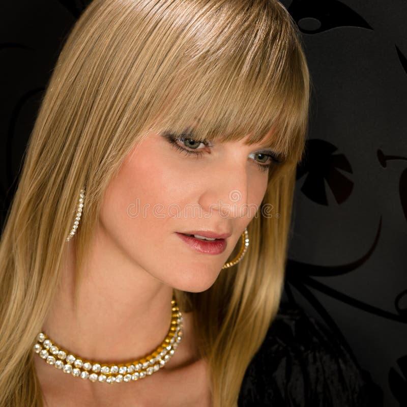 ξανθή γυναίκα πορτρέτου συμβαλλόμενων μερών κοσμήματος φορεμάτων γοητευτική στοκ φωτογραφία με δικαίωμα ελεύθερης χρήσης