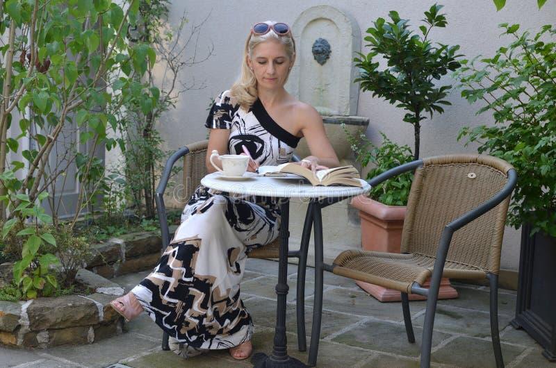 Ξανθή γυναίκα που γράφει σε έναν κήπο στοκ φωτογραφία