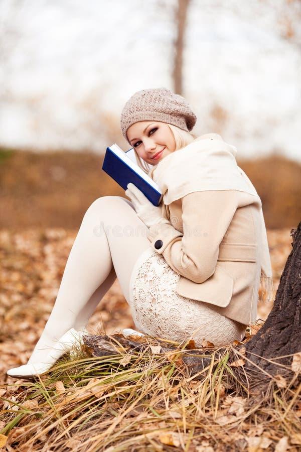 Ξανθή γυναίκα που διαβάζει ένα βιβλίο στοκ εικόνες