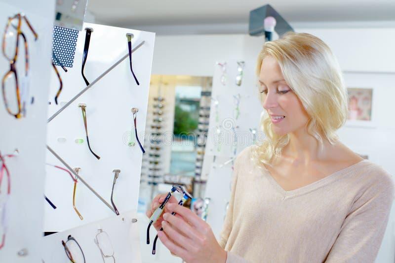 Ξανθή γυναίκα που επιλέγει μεταξύ διαφορετικά eyeglasses στοκ φωτογραφίες με δικαίωμα ελεύθερης χρήσης