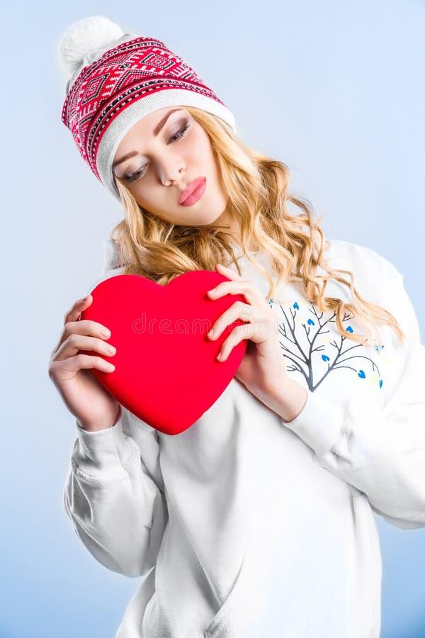 Ξανθή γυναίκα που κρατά μια κόκκινη καρδιά κόκκινος αυξήθηκε στοκ φωτογραφία με δικαίωμα ελεύθερης χρήσης