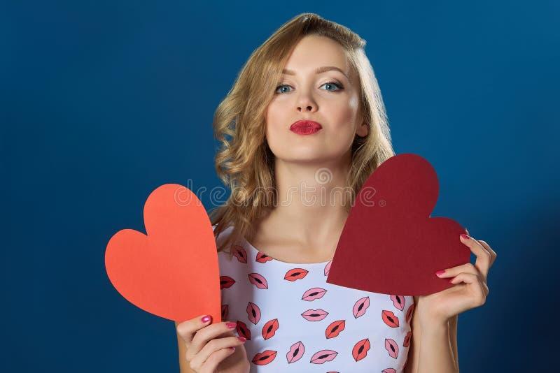 Ξανθή γυναίκα που κρατά δύο καρδιές που φιλούν τα κόκκινα χείλια στοκ φωτογραφίες