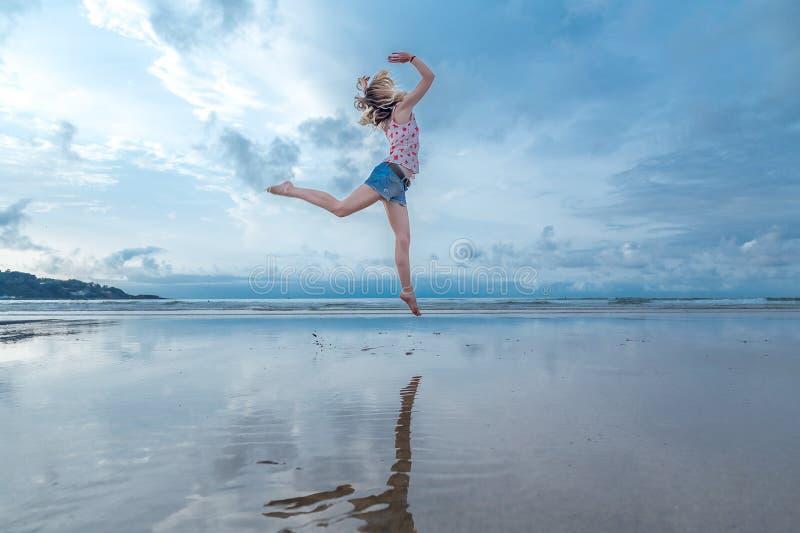 Ξανθή γυναίκα που πηδά πέρα από το νερό στοκ φωτογραφία