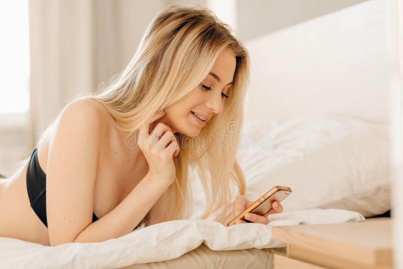 Ξανθή γυναίκα που χρησιμοποιεί το smartphone της όπως αυτή που μένει στο κρεβάτι στη ημέρα αδείας της στοκ εικόνες