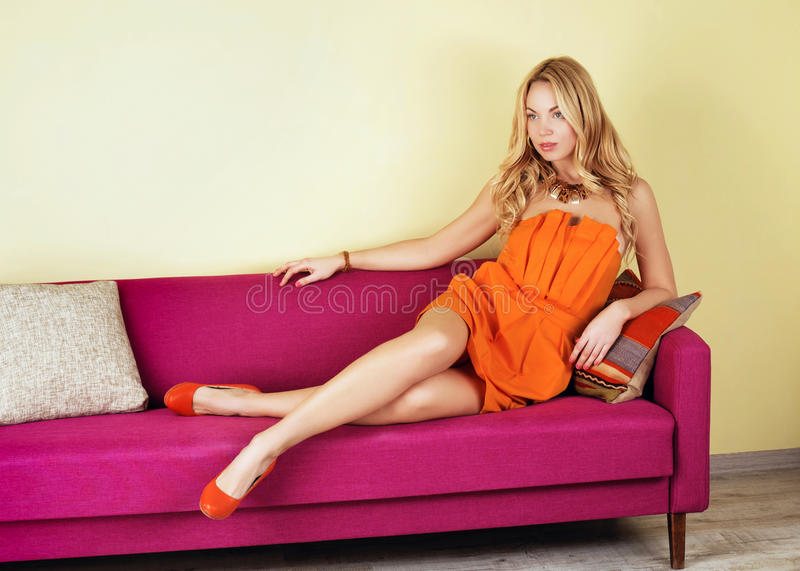 ξανθή γυναίκα σε ένα πορτοκαλί φόρεμα στον πορφυρό καναπέ στοκ εικόνα