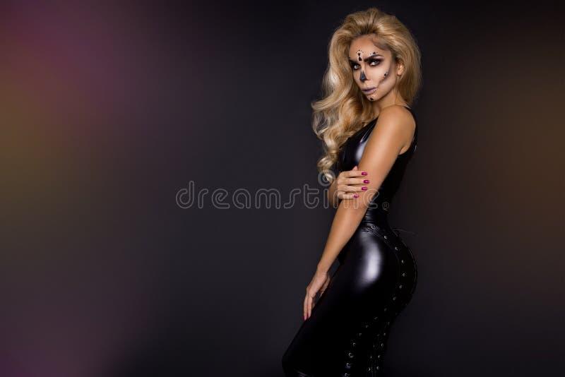 Ξανθή γυναίκα σε αποκριές makeup και εξάρτηση δέρματος σε ένα μαύρο υπόβαθρο στο στούντιο Σκελετός, τέρας και μάγισσα στοκ φωτογραφίες με δικαίωμα ελεύθερης χρήσης