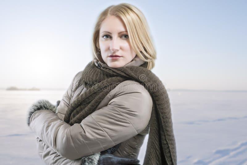 Ξανθή γυναίκα στα θερμά ενδύματα πέρα από τη χειμερινή ανασκόπηση στοκ φωτογραφίες με δικαίωμα ελεύθερης χρήσης
