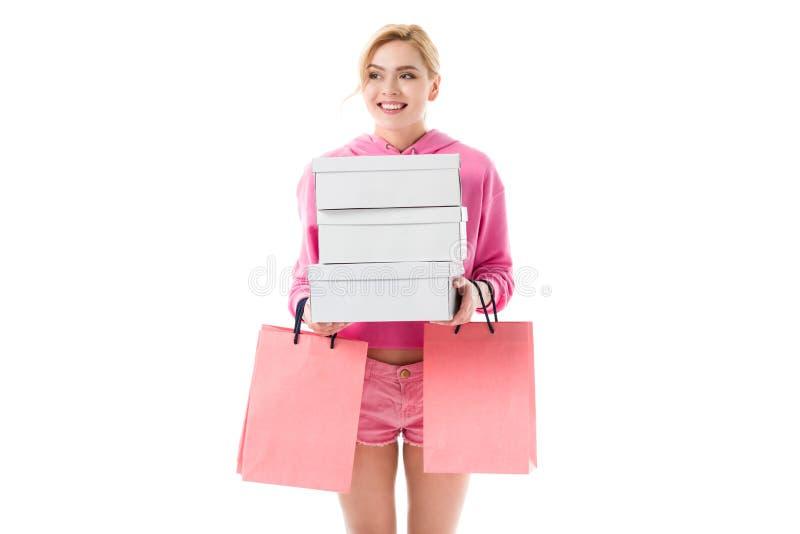 Ξανθή γυναίκα στα ρόδινα ενδύματα που φέρνουν τις τσάντες αγορών στοκ φωτογραφία