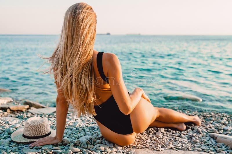 Ξανθή γυναίκα στη μαύρη swimwear χαλάρωση στη θάλασσα στοκ εικόνες με δικαίωμα ελεύθερης χρήσης