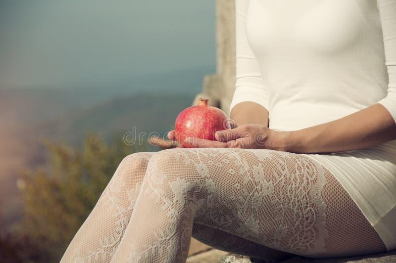 Ξανθή γυναίκα στις άσπρες γυναικείες κάλτσες δαντελλών που κρατά pomegrante στοκ φωτογραφίες