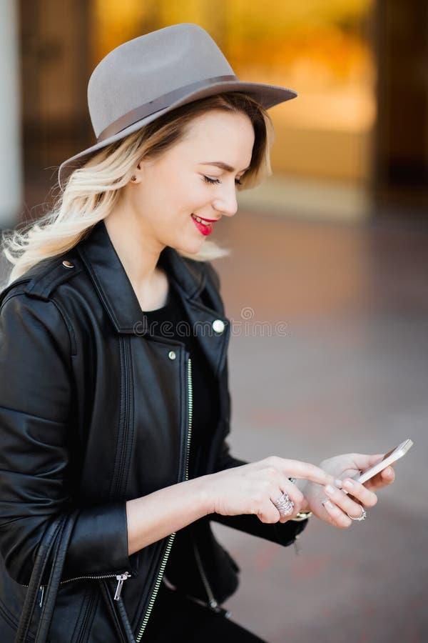 Ξανθή γυναίκα στο σακάκι μαύρων καπέλων και δέρματος και τσάντα που χρησιμοποιούν το κινητό τηλέφωνο στοκ εικόνα με δικαίωμα ελεύθερης χρήσης