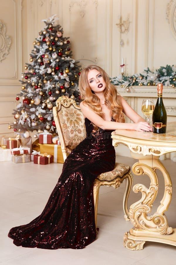 Ξανθή γυναίκα στο φόρεμα βραδιού με το ποτήρι του άσπρης κρασιού ή της σαμπάνιας που εγκαθιστά σε μια καρέκλα στο εσωτερικό πολυτ στοκ εικόνες