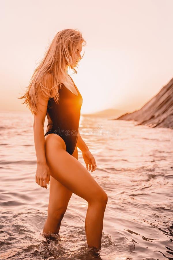 Ξανθή γυναίκα στο swimwear μπικίνι στην ήρεμη θάλασσα με τα χρώματα ηλιοβασιλέματος Κορίτσι στις διακοπές στοκ εικόνα