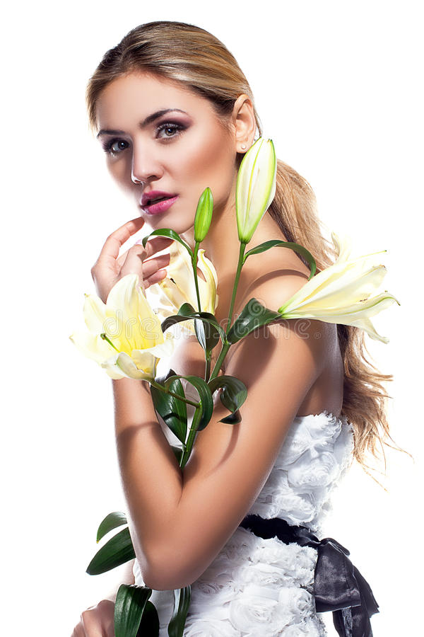 Ξανθή γυναίκα το φρέσκο καθαρό δέρμα και το άσπρο λουλούδι κρίνων που απομονώνονται με στοκ εικόνα