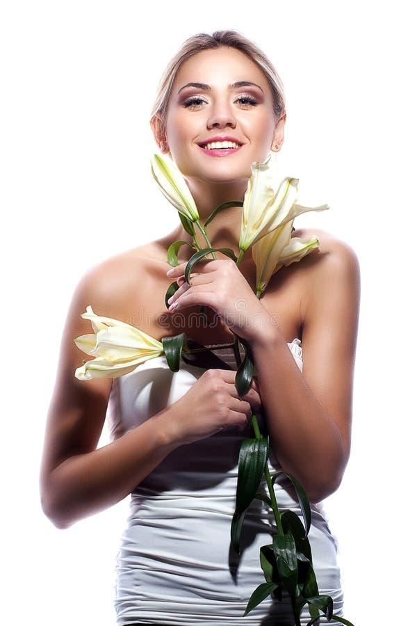 Ξανθή γυναίκα το φρέσκο καθαρό δέρμα και το άσπρο λουλούδι κρίνων που απομονώνονται με στοκ εικόνες με δικαίωμα ελεύθερης χρήσης
