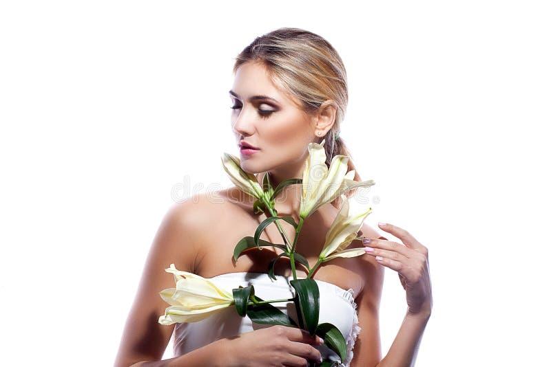 Ξανθή γυναίκα το φρέσκο καθαρό δέρμα και το άσπρο λουλούδι κρίνων που απομονώνονται με στοκ φωτογραφίες
