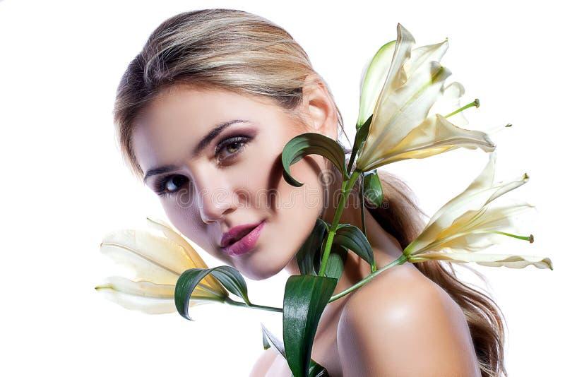 Ξανθή γυναίκα το φρέσκο καθαρό δέρμα και το άσπρο λουλούδι κρίνων που απομονώνονται με στοκ φωτογραφία με δικαίωμα ελεύθερης χρήσης