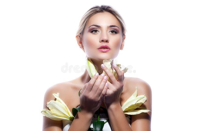 Ξανθή γυναίκα το φρέσκο καθαρό δέρμα και το άσπρο λουλούδι κρίνων που απομονώνονται με στοκ εικόνες