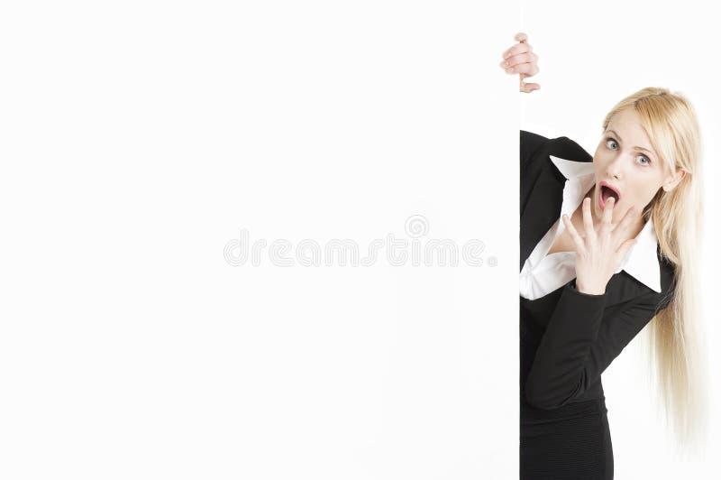 Ξανθή επιχειρηματίας με μια μεγάλη αφίσα στο άσπρο υπόβαθρο στοκ εικόνα