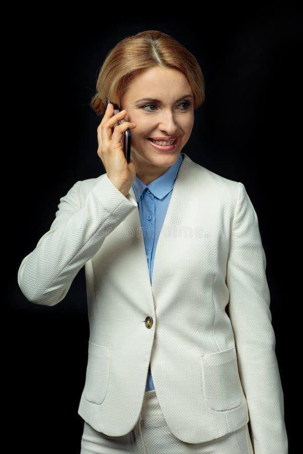 Ξανθή επιχειρηματίας που χρησιμοποιεί το smartphone στο άσπρο κοστούμι στοκ φωτογραφία