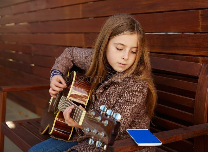 Ξανθή κιθάρα παιχνιδιού εκμάθησης κοριτσιών παιδιών με το smartphone στοκ φωτογραφία