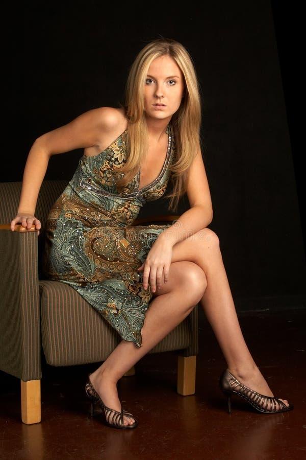 ξανθή κομψή καθισμένη γυναίκα εδρών στοκ εικόνα