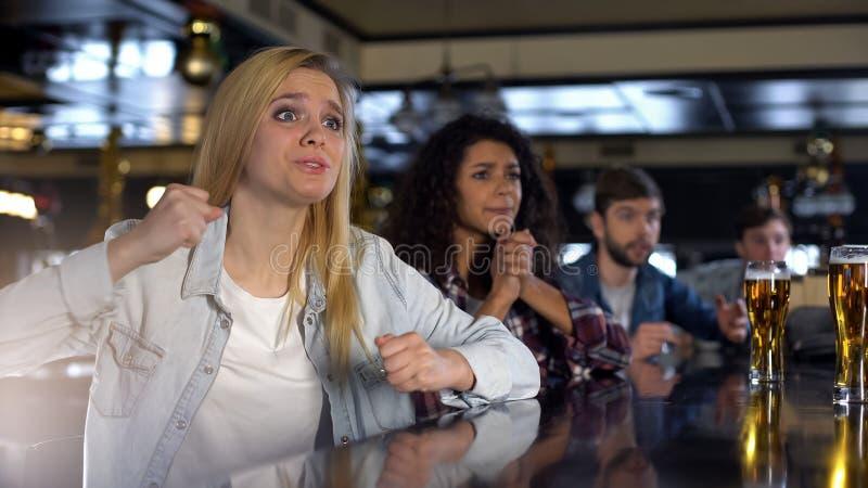 Ξανθή κυρία ενθαρρυντική για την αγαπημένη ομάδα, που κρεμά έξω στο μπαρ με τους φίλους, υποστήριξη στοκ φωτογραφία με δικαίωμα ελεύθερης χρήσης