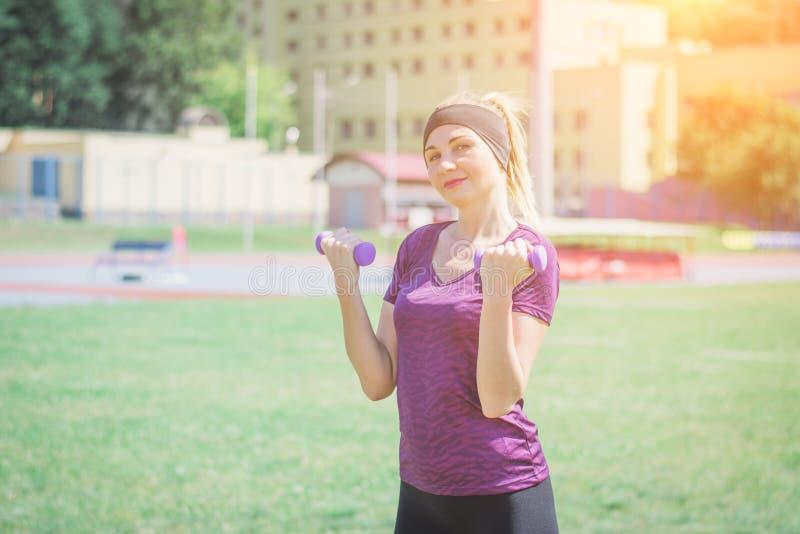 Ξανθή μακρυμάλλης γυναίκα ικανότητας sportswear στη μουσική ακούσματος και να κάνει τις τεντώνοντας ασκήσεις στο γήπεδο ποδοσφαίρ στοκ φωτογραφία με δικαίωμα ελεύθερης χρήσης