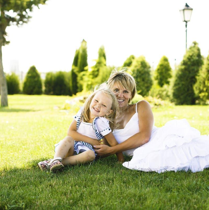 Ξανθή μητέρα με την κόρη που έχει τη διασκέδαση στη χλόη, ευτυχής οικογένεια, λι στοκ εικόνα