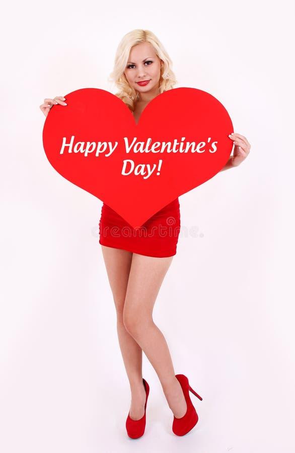 Ξανθή νέα γυναίκα που κρατά την κόκκινη καρδιά με την ημέρα των ευτυχών βαλεντίνων λέξεων στοκ εικόνες με δικαίωμα ελεύθερης χρήσης