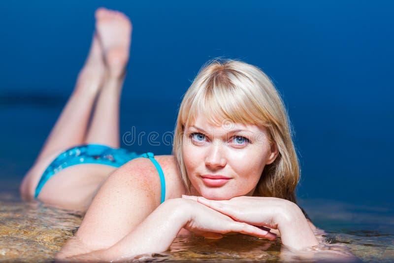 Ξανθή νέα γυναίκα που φορά το μπικίνι, που βρίσκεται στο νερό στοκ φωτογραφίες με δικαίωμα ελεύθερης χρήσης