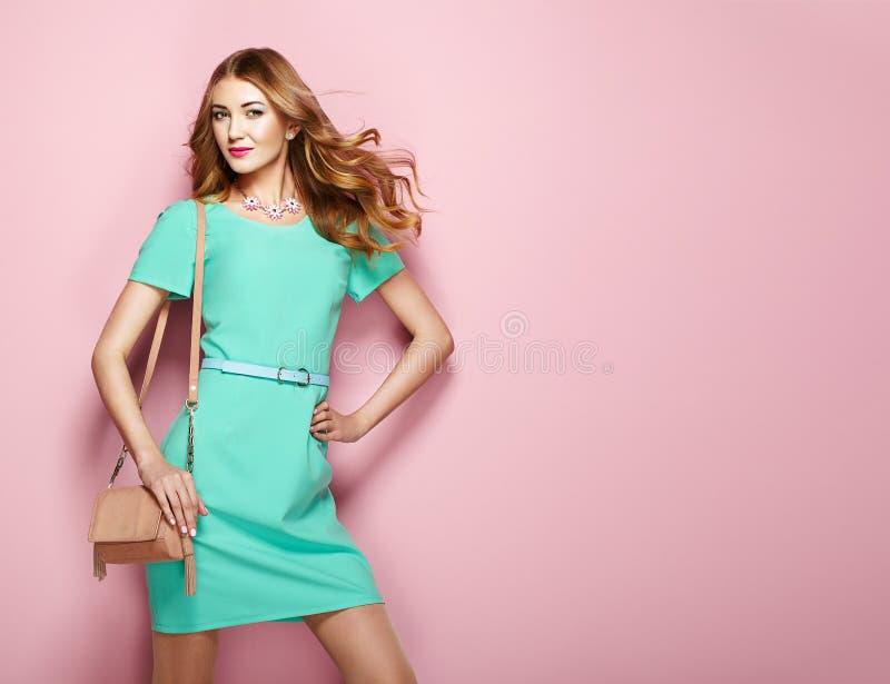 Ξανθή νέα γυναίκα στο κομψό πράσινο φόρεμα στοκ εικόνες