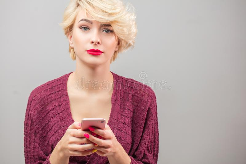 Ξανθή νέα γυναίκα Stylysh που καλεί και που χρησιμοποιεί το τηλεφωνικό isola στοκ εικόνες