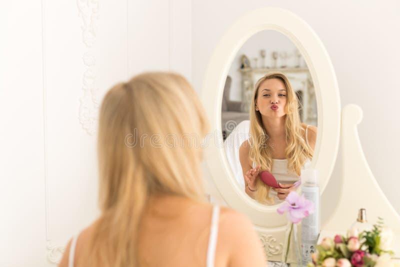 Ξανθή νέα τρίχα βουρτσών γυναικών, όμορφο κορίτσι που κοιτάζει στα φιλιά αέρα χτυπήματος καθρεφτών στοκ εικόνες