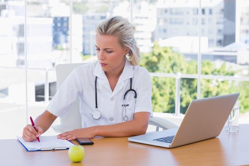 Ξανθή νοσοκόμα που γράφει σε ένα σημειωματάριο στο γραφείο της στοκ φωτογραφίες