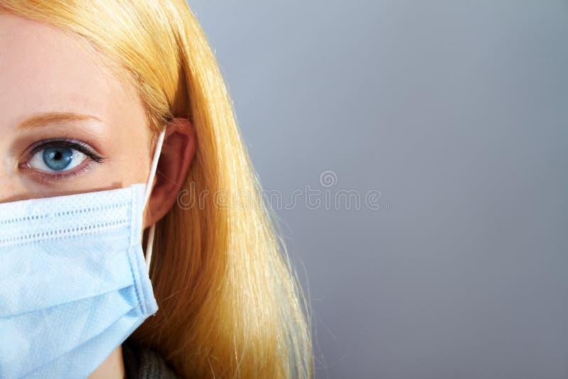 Ξανθή σοβαρή γυναίκα με τη χειρουργική μάσκα στοκ φωτογραφία με δικαίωμα ελεύθερης χρήσης