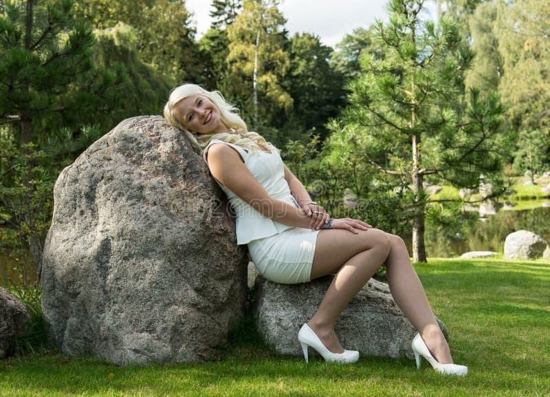 Ξανθή συνεδρίαση γυναικών σε μια πέτρα Νέο κορίτσι που στηρίζεται στη φύση στοκ φωτογραφίες με δικαίωμα ελεύθερης χρήσης