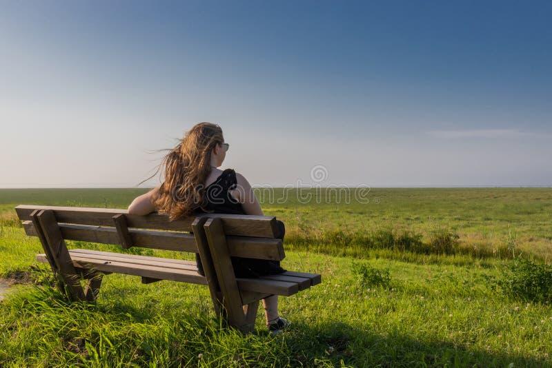 Ξανθή συνεδρίαση κοριτσιών σε έναν πάγκο στοκ φωτογραφίες