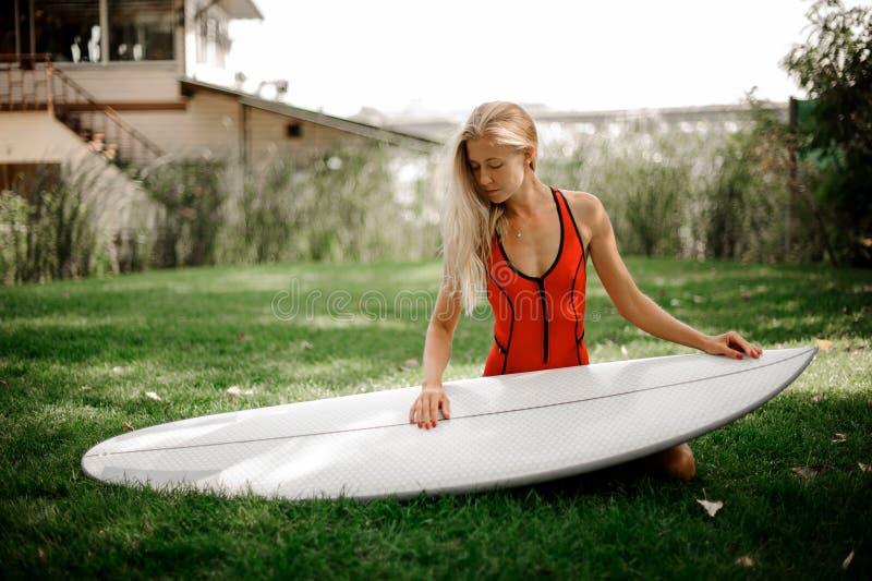 Ξανθή συνεδρίαση κοριτσιών στα γόνατά της που κρατά το wakeboard στοκ φωτογραφία με δικαίωμα ελεύθερης χρήσης