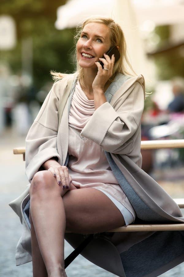 Ξανθή συνεδρίαση γυναικών στον πάγκο και ομιλία στο τηλέφωνο στοκ φωτογραφία