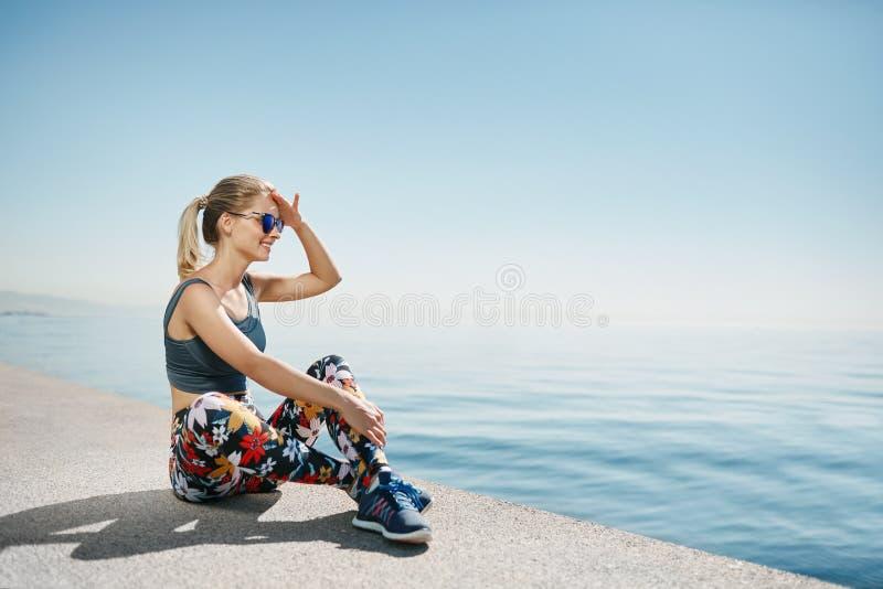 Ξανθή χαλάρωση δρομέων γυναικών ικανότητας μετά από το τρέξιμο πόλεων στοκ φωτογραφία